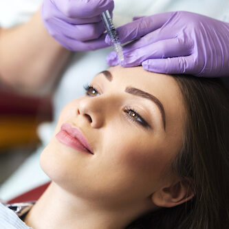 Young woman on a beauty treatment with the filler injection at the beauty clinic.